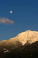 The moon rises over Mount Blandshard from Pitt Meadows, British Columbia, Canada