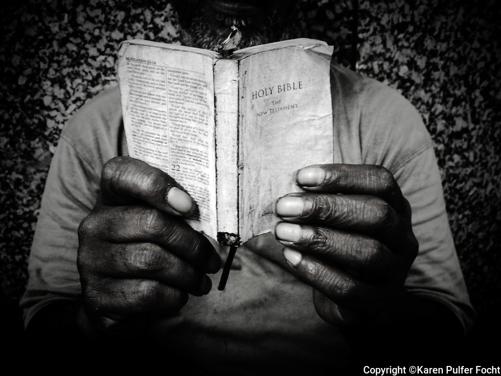 The Hands Of A Homeless Man Holding Bible As He Reads It On