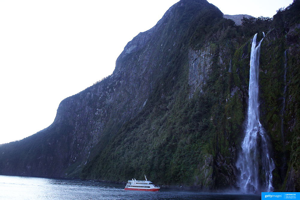 A tourist ship close to the spectacular Stirling Falls on Milford Sound..Milford Sound (Piopiotahi in Ma¯ori) is a fjord in the south west of New Zealand's South Island, within Fiordland National Park and the Te Wahipounamu World Heritage site. It has been judged the world's top travel destination and is acclaimed as New Zealand's most famous tourist destination..Milford Sound runs 15 kilometres inland from the Tasman Sea at Dale Point - the mouth of the fiord - and is surrounded by sheer rock faces that rise 1,200 metres (3,900 ft) or more on either side. Among the peaks are The Elephant at 1,517 metres (4,977 ft), said to resemble an elephant's head and The Lion, 1,302 metres (4,272 ft), in the shape of a crouching lion. Lush rain forests cling precariously to these cliffs, while seals, penguins, and dolphins frequent the waters and whales can be seen sometimes..Milford Sound sports two permanent waterfalls all year round, Lady Bowen Falls and Stirling Falls. After heavy rain many hundreds of temporary waterfalls can be seen running down the steep sided rock faces. .The beauty of this landscape draws thousands of visitors each day, with between 550,000 and 1 million visitors in total per year. This makes the sound one of New Zealand's most-visited tourist spots, and also the most famous New Zealand tourist destination.  Milford Sound, New Zealand. 29th April 2011. Photo Tim Clayton