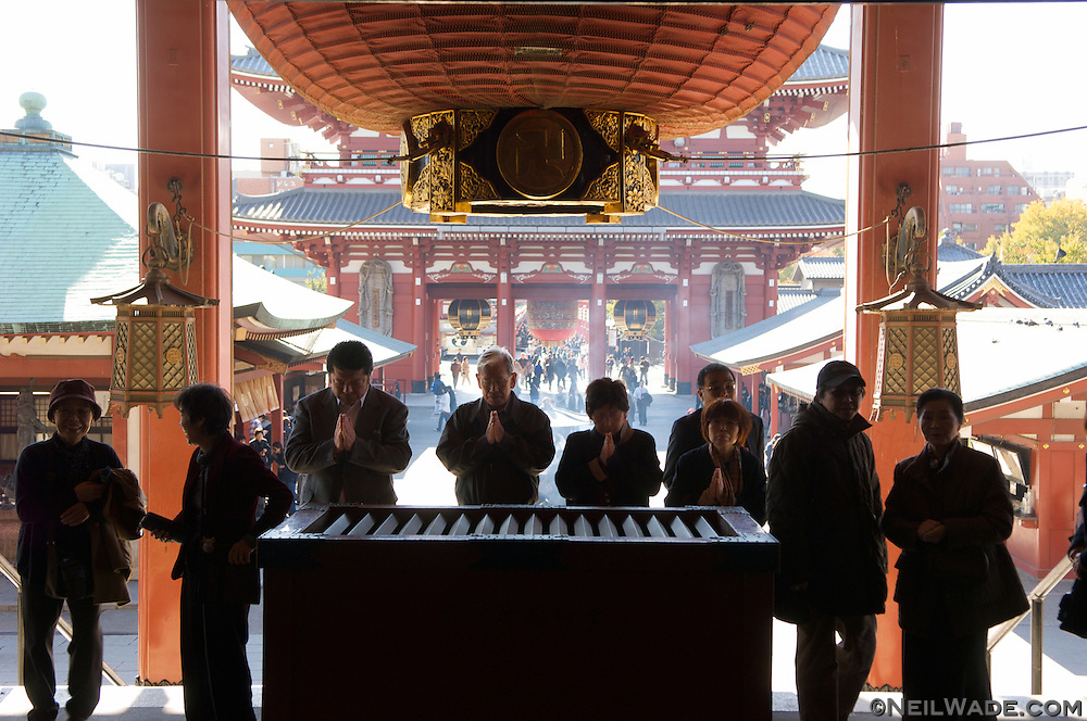 The Japanese people mix their religions.  Shinto, Buddhism and sometimes Christianity all seem to go hand in hand.  Here, a group of people pray at the famous temple Senso Ji, near Asakusa Koen, in Tokyo, Japan.