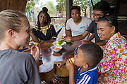 ICS volunteers Tania Tuzizila, Vannak Uch, Luna Boran & Keira Thompson sit down with the family  of their host home to eat mango, in the village of in Banteay Char, near Battambang, Cambodia.