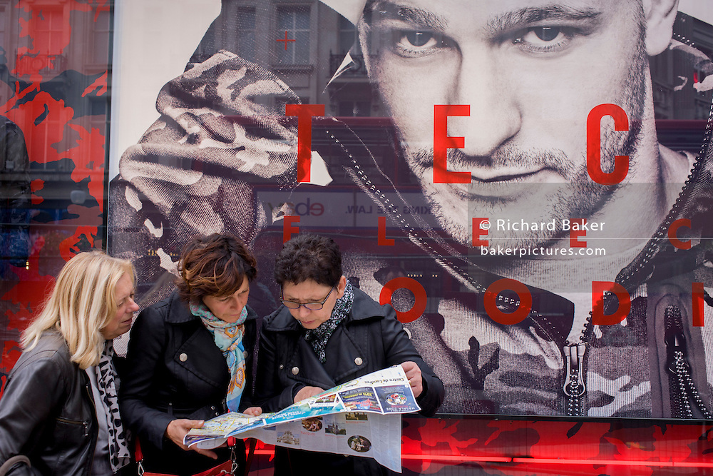 Women tourists pause to look at a map of central London (Londres) beneath a large male model's face advertising Nike's Tech Fleeces.