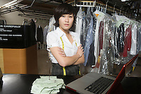 Woman standing infront of a laptop  working in a laundrette