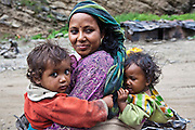 A mother and children are part of migrant community resurfacing a road in the Himalayas, India.  The migrant community is given education and information support by the Pragya organization who have a project helping in high altitude areas across the Himalayas.