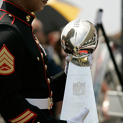 June 8, 2010; Buras, LA, USA; The reflection of a member of the United States Marine Corp can be seen as he carries in the Vince Lombardi Trophy from the New Orleans Saints Super Bowl XLIV win over the Indianapolis Colts, the trophy was on display for fans during a rally held at Fort Jackson. The entire team held a rally at Fort Jackson and visited with members of the small Plaquemines Parish fishing community of Buras that has been impacted by the oil spill. Mandatory Credit: (Photographer: Derick E. Hingle).