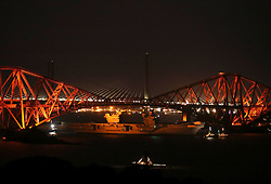 HMS Queen Elizabeth, one of two new aircraft carriers for the Royal Navy, is pulled by tugs under the Forth Rail Bridge in the Firth of Forth, as she sets sail to begin her sea worthiness trials.