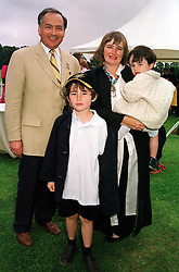 MR & MRS ALASTAIR STEWART, he is the newsreader and tv presenter, with their children FREDDIE (standing) and OSCAR, at a polo match in Sussex on 23rd July 2000.OGI 122