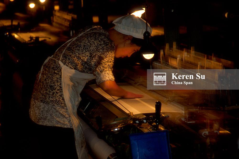Woman weaving silk threads into fabric in the factory, Hotan, Xinjiang Province, Silk Road, China