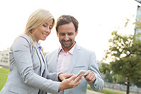 Happy business couple using smart phone at park