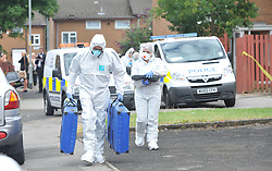 © London News Pictures. 29/07/2013. Manchester, UK. Police forensics officers at the scene on Delta Walk, in Moston, Manchester where A father has been stabbed to death and his 13-year-old child left in a critical condition. A second man, who also suffered stab wounds,  died after he crashed a hijacked car into a nearby pub. Photo credit Steve Allen/LNP