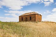 dilapidated old brick farm house in a field near Pallamana, South Australia, Australia