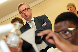 ©Licensed to London News Pictures. 04/04/2014<br /> Brooke Weston Academy, Corby, Northamptonshire. Secretary of State for Education Michael Gove MP visiting Brooke Weston Academy in Corby as part of a fact finding tour of free schools. Pictured, Michael Gove MP in Year 12 chemistry lesson<br /> Photo credit: Steven Prouse/ LNP
