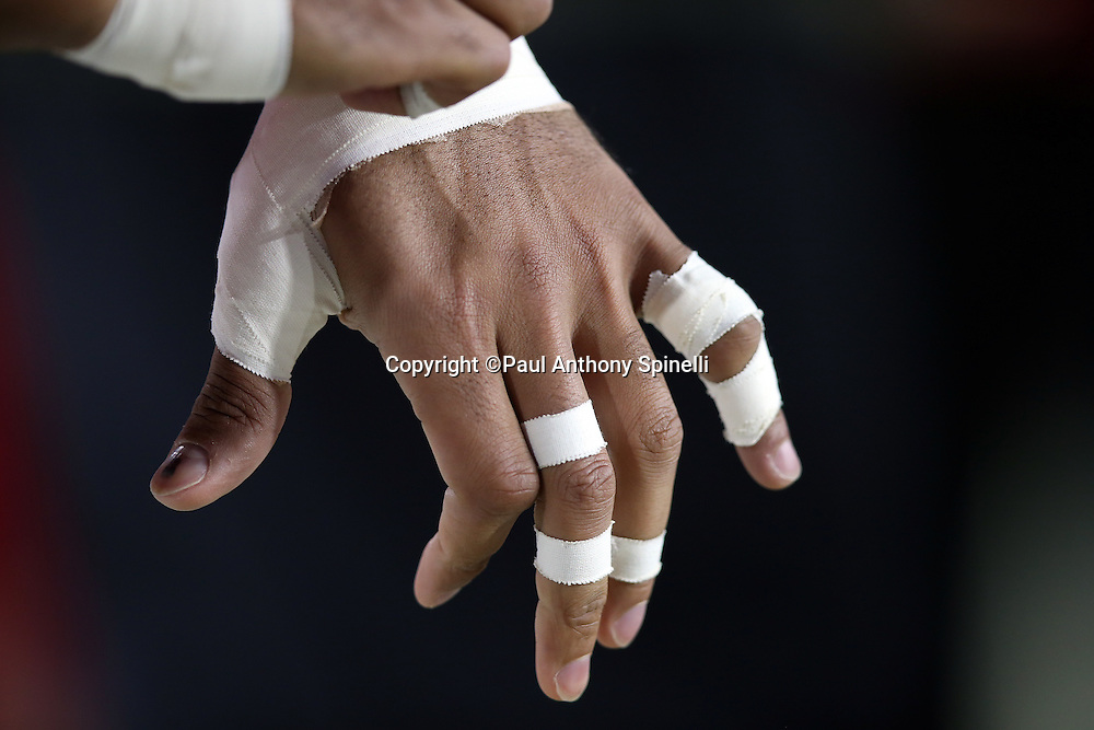 An Arizona Cardinals player adjusts the tape on his fingers during the NFL NFC Divisional round playoff football game against the Green Bay Packers on Saturday, Jan. 16, 2016 in Glendale, Ariz. The Cardinals won the game in overtime 26-20. (©Paul Anthony Spinelli)