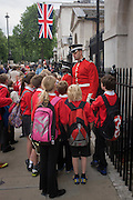 British schoolchildren on a daytrip to the capital enjoy a chance encounter with guardsmen at Horseguards on London's Whitehall. Gathering around the two troops, they talk to the caucasian man rather than the smaller man of afro-caribbean descent, both wearing the scarlet uniform tunics of the British Household Cavalry. This regiment is classed as a corps in its own right, and consists of two regiments: Life Guards (British Army) and the Blues and Royals (Royal Horse Guards and 1st Dragoons). They are the senior regular regiments in the British Army, with traditions dating from 1660.