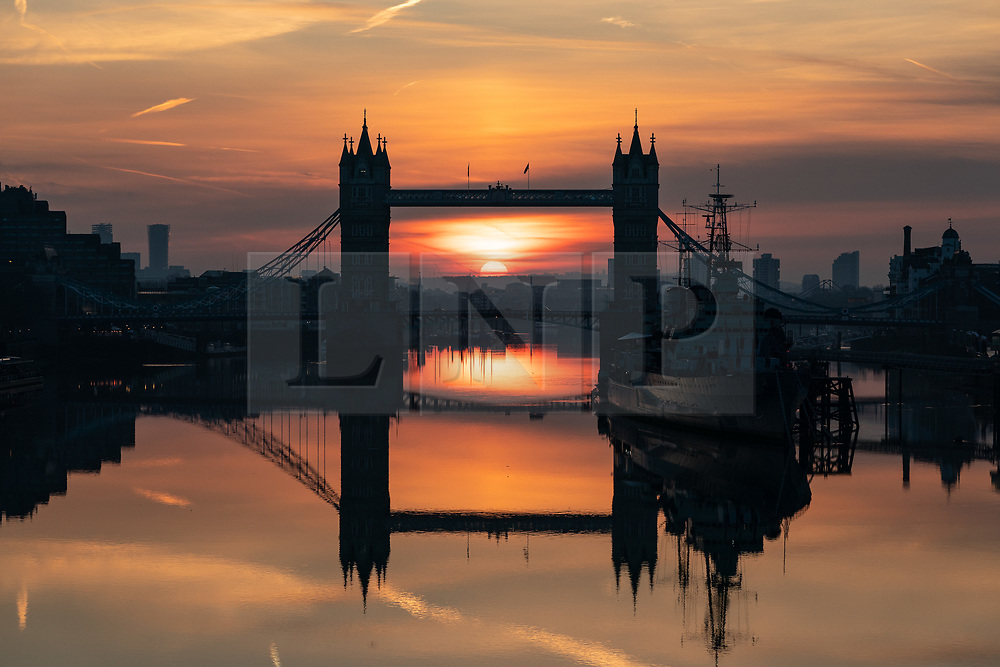 © Licensed to London News Pictures. 17/02/2019. London, UK. The sun rises through Tower Bridge in London on a clear day in the capital. Temperatures are set to rise to 14 degrees Celsius later today, unseasonably warm for February. Photo credit : Tom Nicholson/LNP