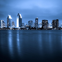 Photo of San Diego at night skyline buildings along San Diego Bay. Photo is toned blue, high resolution and was taken in 2012.