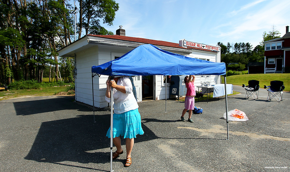 Resident Nancy Martland, puts up a tent, with the help of Katherine Duphine, 7, of Franconia, out front of the Sugar Hill post office in preparation for a retirement party for postal woker Bob Clark, in Sugar Hill, N.H.,  Saturday, June 23, 2012.  (Cheryl Senter for the Boston Globe)