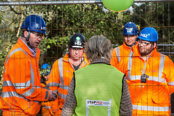 Harefield, UK. 7 February, 2020. A woman who lives close to the proposed route of the HS2 high-speed rail link observes HS2 engineers erecting Heras fencing to surround three environmental activists from Extinction Rebellion who have climbed a veteran oak tree close to the Harvil Road wildlife protection camp in order to try to protect it from felling. HS2 are expected to try to fell large numbers of mature trees in the immediate vicinity over the weekend even though the high-speed rail link is still awaiting Boris Johnson's approval.