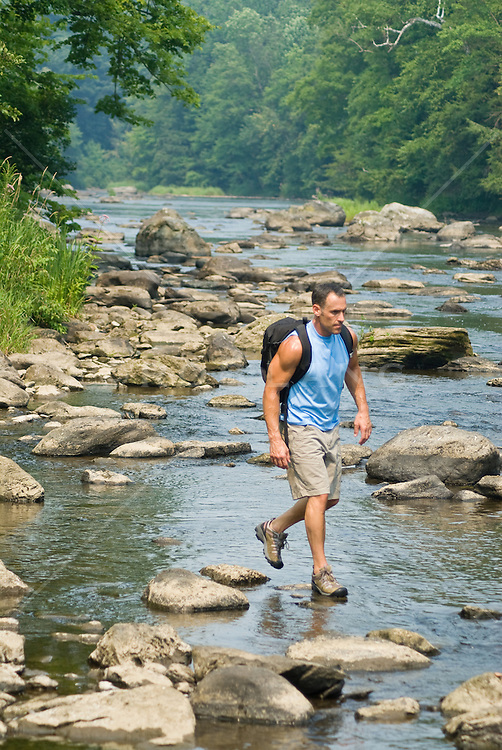 man outdoors on a river walking on rocks