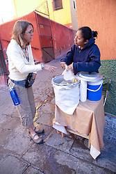 North America, Mexico, Guanajuato State, Guanajuato,  woman buying hot tamales from street vendor.  The historic city of Guanajuato is a UNESCO World Heritage Site.