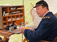 Old Bethpage, New York, USA - July 21, 2012: BOB HANSEN (R) of Sea Cliff, NY, portrays Company Clerk eating lunch, at re-creation of Camp Scott, a Union Army training camp, at Old Bethpage Village Restoration, to commemorate 150th Anniversary of American Civil War.