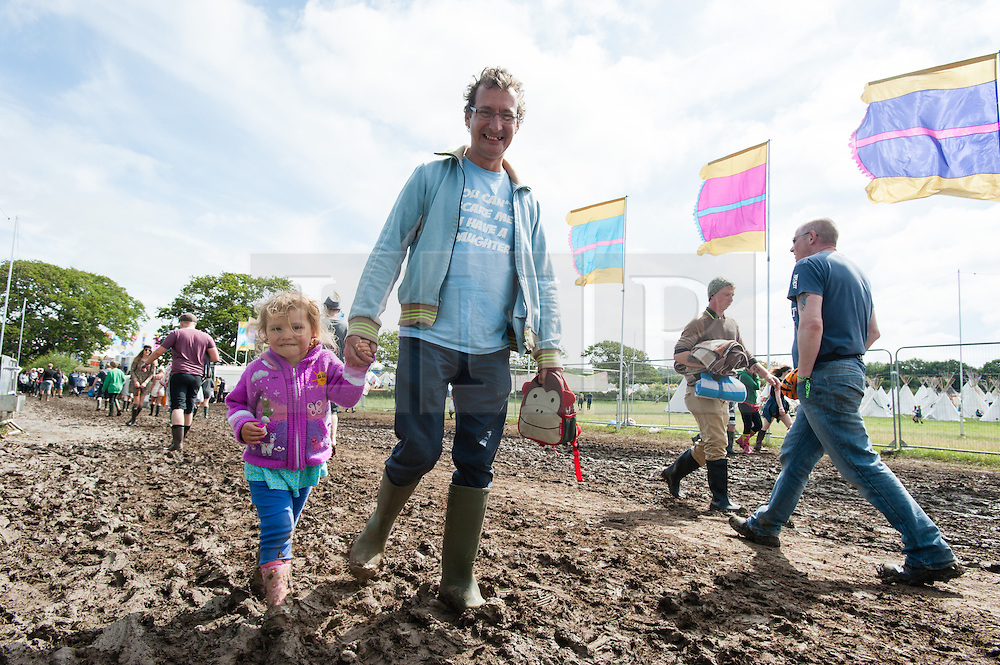 © Licensed to London News Pictures. 13/06/2015. Isle of Wight, UK. A father and her young daughter festival goers splash through the mud, eyes down, at Isle of Wight Festival 2015 on the morning of Saturday Day 3.  Yesterday suffered torrential rain all afternoon and evening, after a first day of warm sun.  This years festival include headline artists the Prodigy, Blur and Fleetwood Mac.  Photo credit : Richard Isaac/LNP