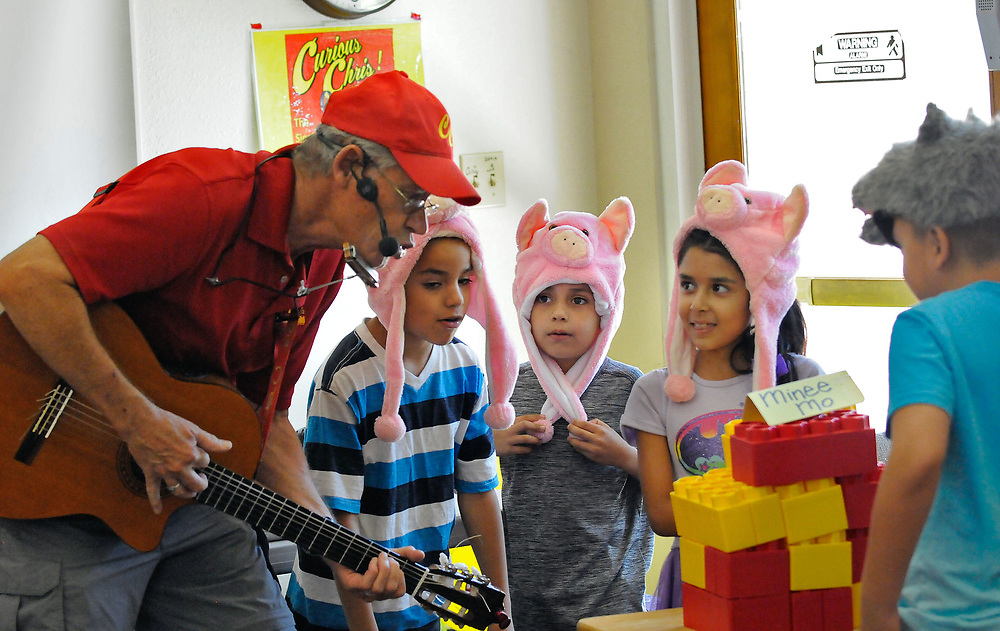 jt071117a/ a sec/jim thompson/ Curious Chris Harrell helps the three little pigs and the big bad wolf try to blow over the house of bricks. left to right on the pigs are Dominic Mata-9 and his brother Adrian Mata-7 and Eliana Whetten-8. the wold was Robert Martinez,Jr. -8. At the South Valley Library Harrell does his version of the three little pigs as the 6 little pigs and uses science and music for the kids to understand the story and hands-on envolvement. Tuesday,  July. 11, 2017. (Jim Thompson/Albuquerque Journal)