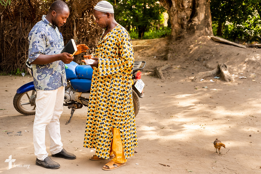 A Sierra Leonean pastor with the Christ Evangelical Lutheran Church—Sierra Leone (CELC—SL) prays with a man who received his medications after treatment on the fourth day of the LCMS Mercy Medical Team on Thursday, May 10, 2018, in the Yardu village outside Koidu, Sierra Leone, West Africa. LCMS Communications/Erik M. Lunsford