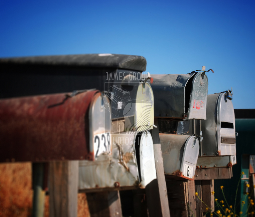 A row of grungy mailboxes in the country