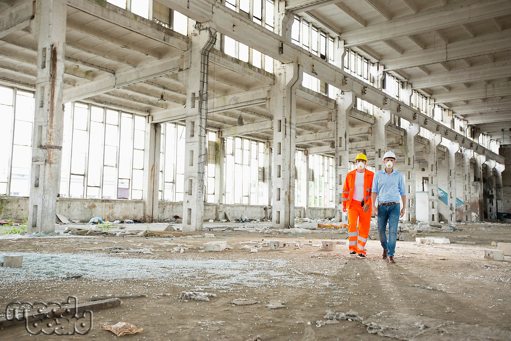 Full length of construction workers in protective workwear walking at site