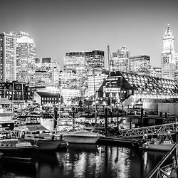 Boston skyline at night black and white photo with Boston Harbor waterfront, boats, and downtown Boston buildings.