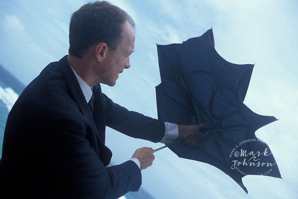 Businessman opening umbrella in trying circumstances
