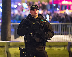 © Licensed to London News Pictures . 31/12/2017. Manchester, UK. Armed police patrol in Albert Square as thousands watch as Manchester celebrates the start of 2018 , with a fireworks display in front of the Town Hall in Albert Square . This year's celebration sees additional security, including concrete barriers around the square and bag searches and the event includes a poetry reading by Tony Walsh , in memory of those who were killed at a terrorist attack after at the Manchester Arena in May 2017. Photo credit: Joel Goodman/LNP