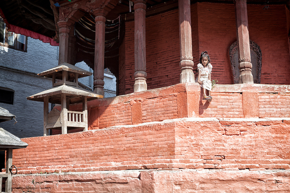 A young Nepali girl sits on a temple wall in Kathmandu's Durbar Square.