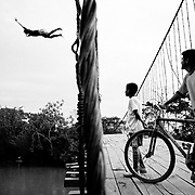 A young daredevil impresses onlookers as he dives from a suspension bridge into the Rio Caquan.<br />