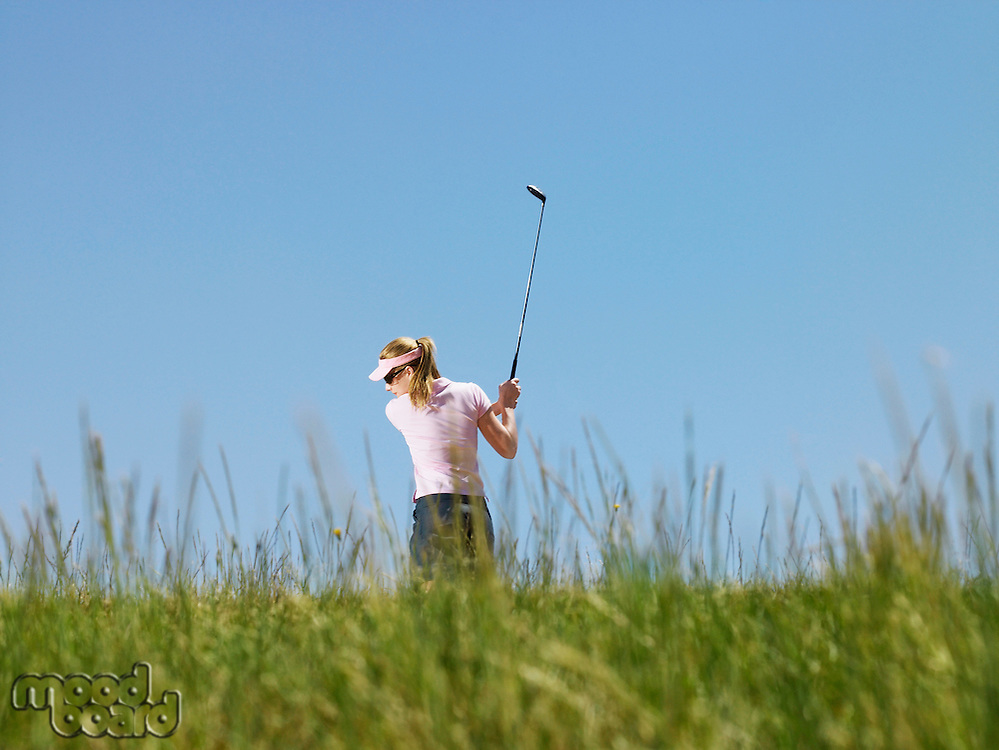Young female golfer driving ball back view