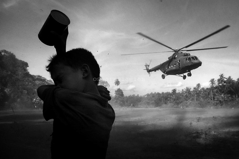 boy waits ofr an Indonesian army helicopter to land as aid is brought to relief the village of Lubuk Anau on October 9, 2009 in Padang, Indonesia. The first quake on September 30 was a magnitude of 7.6, 85km under the sea north-west of Padang with the second quake measuring 6.8 a day later on October 1