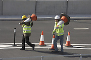 Construction workers carry cones in car parking area of  newly-opened London Heathrow Airport's Terminal 5 building.