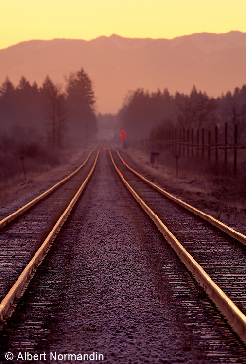 Rail road tracks leading off to mountains at sunrise