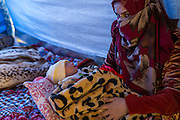 Marwa Hussein, 22, holds her 3-day-old baby inside a tent in Khazer camp, located approximately 40km west of the Kurdish city of Erbil, on December 4, 2016. Her and her husband fled their home in Mosul in order to reach a hospital before the baby was born. Marwa was 9 months pregnant when they fled.