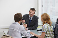 Couple in estate agents real estate agent handing man pen