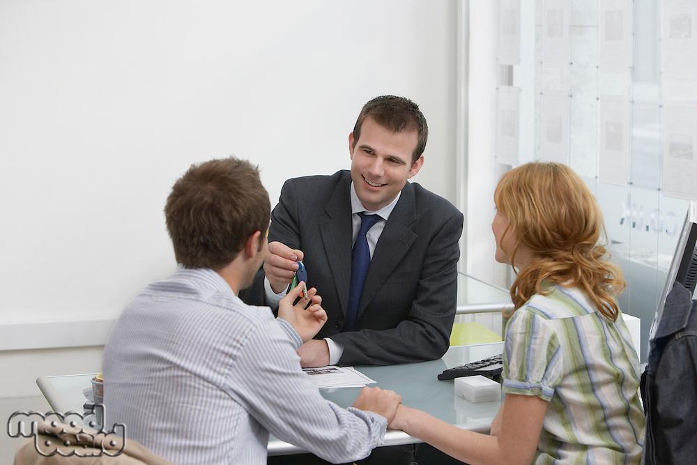 Couple in estate agents real estate agent handing man pen