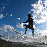 Costa Rica, Nicoya Peninsula, Young man surfing on breaking waves at Playa Grande