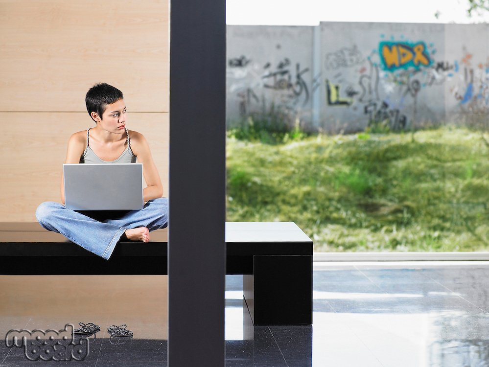 Young woman sitting down using laptop indoors