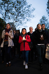 """People praying with candles during an evening of prayer and songs organized by Catholics community the day after Notre Dame Cathedral blaze with a march organized from Saint-Sulpice church to Saint Michel and finally next to Notre Dame Cathedral in Paris early on April 16 the day after the beginning of the fire , 2019. A huge fire that devastated Notre-Dame Cathedral is """"under control"""", the Paris fire brigade said early on April 16 after firefighters spent hours battling the flames. Photo by Raphael Lafargue/ABACAPRESS.COM"""