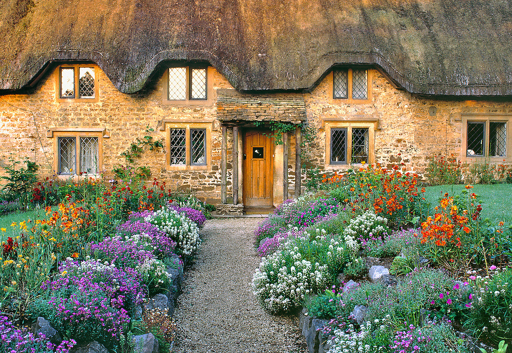 Early morning light warms the golden Cotswold stones of a thatched cottage near Chippenham, England.