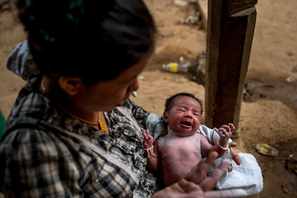 A woman sits with her newborn baby in the village of Khoc Kham, along the banks of the Mekong river. The village is not connected to the main electrical grid and many residents operate their own turbines to power lights and sometimes small appliances.