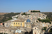 Hill town of Ragusa Ibla, in Sicily, Italy. The town is split into the lower and older town of Ragusa Ibla, and the higher upper town of Ragusa Superiore, separated by the Valle dei Ponti. The yellow facade is the Palazzo Distefano Sortino Trono, built 1778-93, and the blue dome is the church of Santa Maria dell'Itria, rebuilt in 1740. Ragusa is built on the site of an ancient city, inhabited by Sicels, Greeks, Carthaginians, Romans, Byzantines, Arabs and Normans. In 1693 it was devastated by an earthquake, and was rebuilt in the Baroque style. The town forms part of the Late Baroque Towns of the Val di Noto UNESCO World Heritage Site. Picture by Manuel Cohen