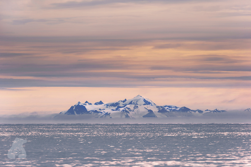 It's autumn in Svalbard and the sun will soon disappear below the horizon for several months, giving way to the Polar Night. For now, the whole archipelago is bathed by the warm hues of the fast-changing season. Here, the snow-covered mountains of Danskøya island rise from the frigid Arctic Ocean.