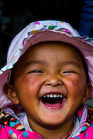 A young Tibetan girl laughing. Tibet (Xizang), China.